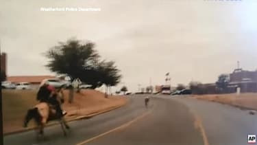 A cowboy chases a runaway steer through Weatherford, Texas