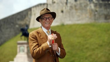 British actor Sir John Hurt poses after being awarded a knighthood by Queen Elizabeth II