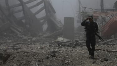 An Iraqi Federal police officer walks among the ruins in Mosul.