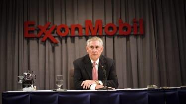 Rex Tillerson sits beneath an ExxonMobil sign