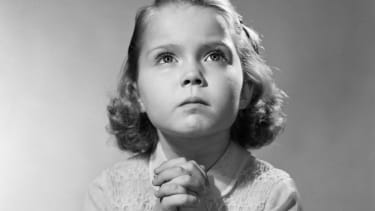 A young girl prays before bed.
