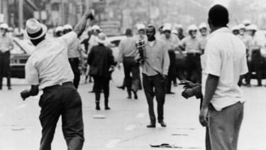 A man hurls a shoe at police