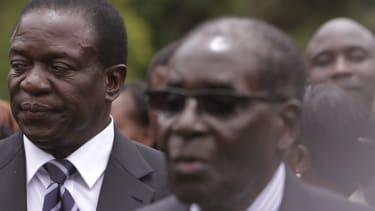 Emmerson Mnangagwa (left) Vice President of Zimbabwe stands behind Zimbabwean President Robert Mugabe in Dec. 2014.