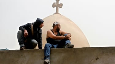 Egyptian Christians sit on the wall of the Coptic cathedral in Cairo, April 8.