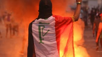 A protester makes the peace sign in Baghdad.