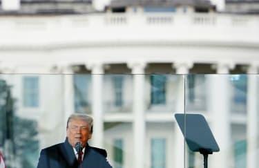 Trump speaks behind bulletproof glass.