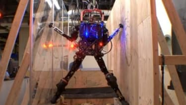"""""""Pet-Proto,"""" the military's human-like robot, navigates a pit a potential danger in an obstacle course."""