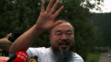 Dissident Chinese artist Ai Weiwei waves from his studio after unexpectedly being released on bail Wednesday.