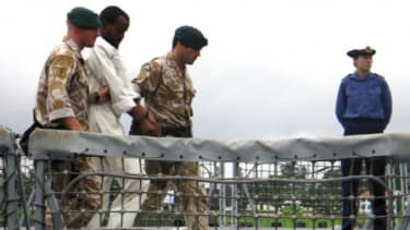 British Navy officials escort a suspected Somali pirate from a ship in April. The number of pirate attacks worldwide rose 10 percent in 2010.
