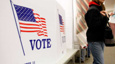 A woman leaves a voting booth.