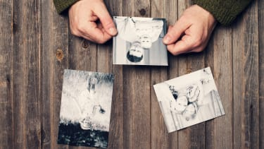 Person looks at old photo of baby and father
