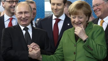 Vladimir Putin and Angela Merkel laugh.