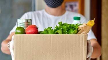A person holds a box of groceries.