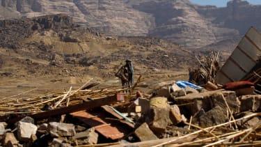 A man in Yemen examines a house leveled by an air raid