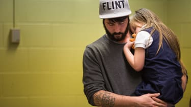 A father comforts his daughter after her free lead screening on Jan. 26, 2016.