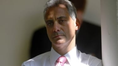 Rahm Emanuel stands behind the scenes at the White House as Obama gives a speech on the economic recovery.