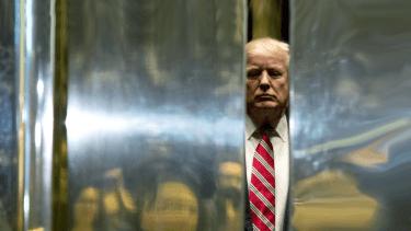 President Trump peeks through some doors.