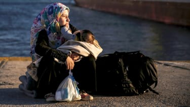 A Syrian refugee holds her baby after arriving in Greece.