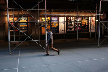 People walk through the empty Broadway theater district one year after it was closed due to Covid-19 restrictions on March 12, 2021 in New York City.