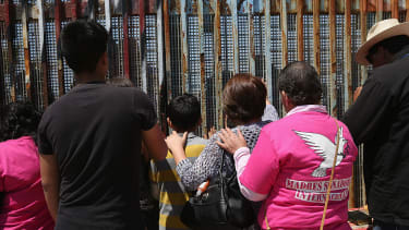 DREAMERs and their parents pray at a Mexican border fence.