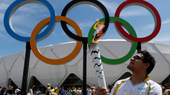 Brazilian designer Glauber Penha takes part in the Olympic Flame torch relay.