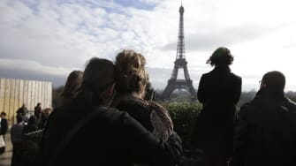 People observe a minute of silence at the Place de Trocadero in Paris on November 16, 2015