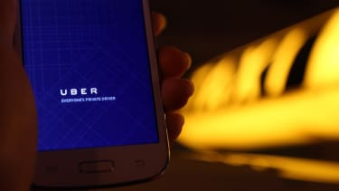 A phone shows the Uber app