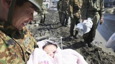 A soldier smiles at the four-month-old baby girl who was rescued from beneath a pile of debris three days after the quake hit.