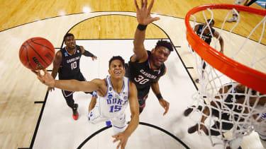 A Duke player tries to make a slam dunk.