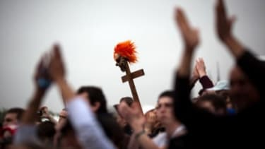 """A cross with a clown mask is held during the National Atheist Organization's """"Reason Rally"""" march last month."""