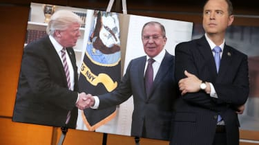 Rep. Adam Schiff stands before photo of Trump and Lavrov