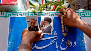 A mourner carries photos during the funeral of a victim of the Tehran attacks on June 7.