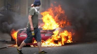 A masked man walks past a burning car in London
