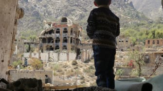A boy stands in the rubble of a home in Yemen.