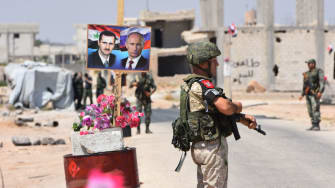 Members of Russian and Syrian forces stand guard near posters of Syrian President Bashar al-Assad and his Russian counterpart Vladimir Putin in Syria.
