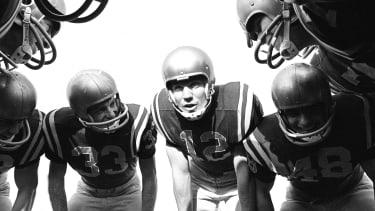 Football players huddle, 1963.