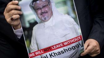 A man holds a poster showing Jamal Khashoggi.