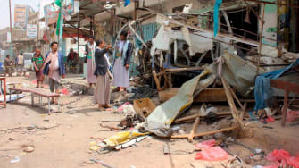 Yemenis gather next to the destroyed bus at the site of a Saudi-led coalition air strike, that targeted the Dahyan market the previous day in the Huthi rebels' stronghold province of Saada on