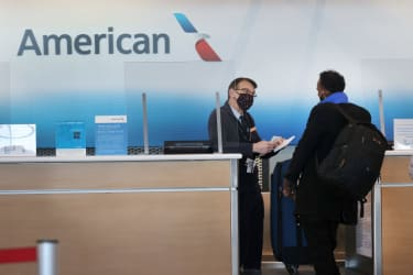 An American Airlines ticket agent checks in a passenger.