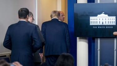 Donald Trump is escorted out of the White House briefing room.