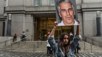 A woman holds a picture of Jeffrey Epstein.