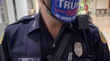 A Miami police officer in a pro-Trump mask at a voting site.