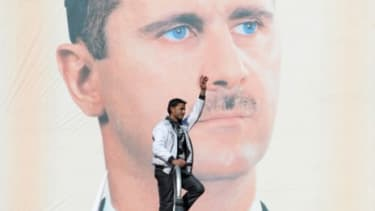 """A protester stands in front of an oversized poster of President Bashar al-Assad: Opposition leaders say Monday's municipal elections were """"utterly meaningless."""""""