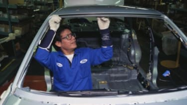 An employee in Ford's mexico-based factory works on a car.