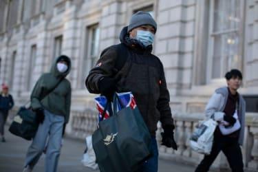 People walk around London in masks