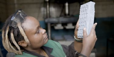 Nzambi Matee inspects one of her factory's recycled bricks.