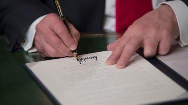 President Trump signs.