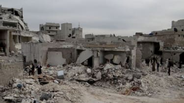 Syrian citizens inspect the desolated site of a government airstrike in Aleppo on March 19.