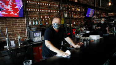 A bartender wearing a face mask wipes down the bar.
