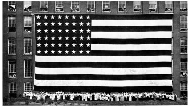 Workers beneath an American flag.